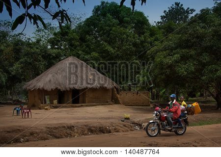 Yongoro Sierra Leone - June 03 2013: West Africa the village of Yongoro in front of Freetown a family through the village with their own motorcycle
