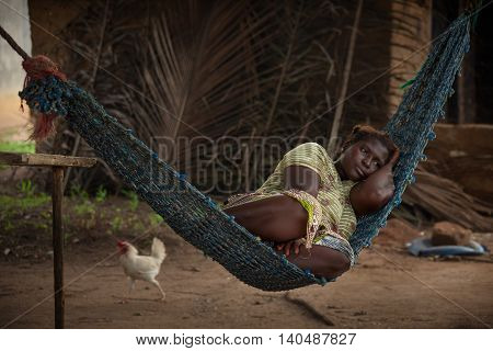 Yongoro Sierra Leone - June 03 2013: West Africa the village of Yongoro in front of Freetown young woman resting on a hammock in the background passes a chicken