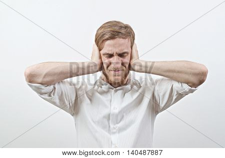 Sad Unpleasant Young Adult Male in White Shirt Covers His Ears