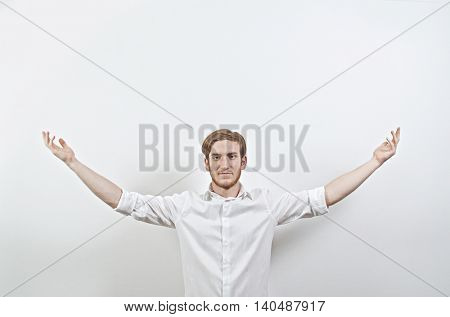 Young Adult Male in White Shirt Gesturing, Arms Raised, Wide Open