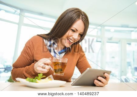 Young woman using her tablet while drinking tea in cafe.Woman having fun chatting on her tablet.