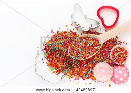 Baking background with ingredients: colorful sugar sprinkling cutter for cookies mold for cake isolated on white background empty space for text top view