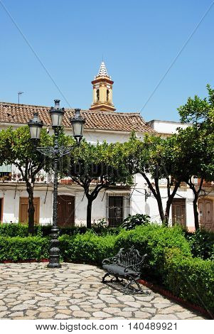 Streetlight and bench in the Plaza las Flores with the church tower to the rear Estepona Malaga Province Andalucia Spain Western Europe.