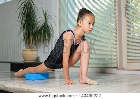 Stretching Little japanese Girl. Attractive beautiful Asian girl doing gymnastics exercises in hall rhythmic gymnastics. window jalousie in the background.
