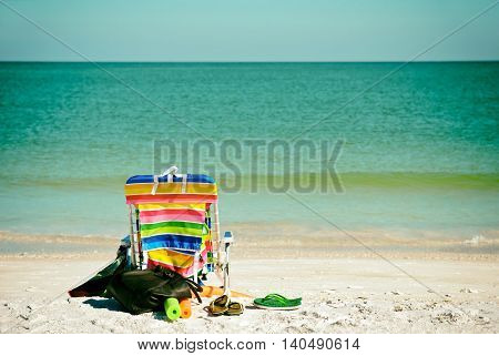 Bright Color Beach Chair with flip flops floats and bag on the Beach