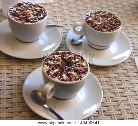 Several cups of coffee with milk on brown background