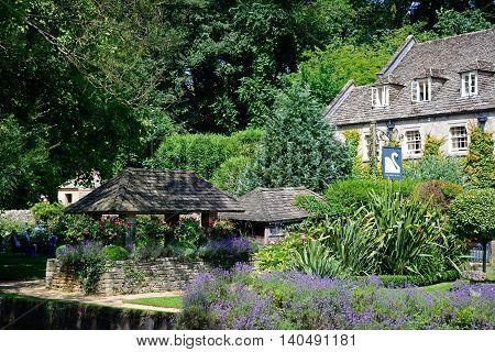 BIBURY, UNITED KINGDOM - JULY 20, 2016 - View across the trout farm garden towards The Swan Hotel Bibury Cotswolds Gloucestershire England UK Western Europe, July 20, 2016.