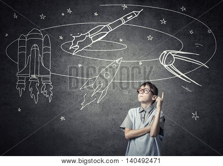 Cute boy of school age dreaming he is astronaut