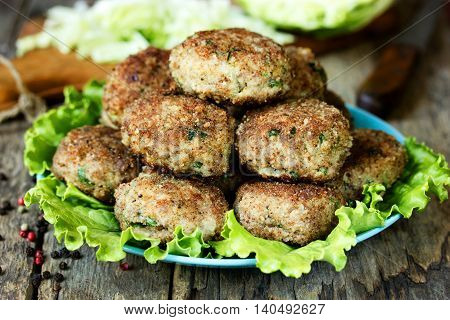 Meat cutlets with cabbage on a plate with green salad lettuce. Rustic food recipe selective focus