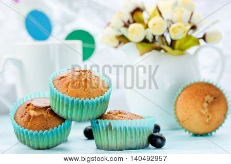 Delicious muffins on the festive table with a bouquet of flowers and garland selective focus