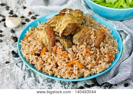 Traditional uzbek food called pilaf cooked with fried lamb meat rice carrot onion and garlic selective focus