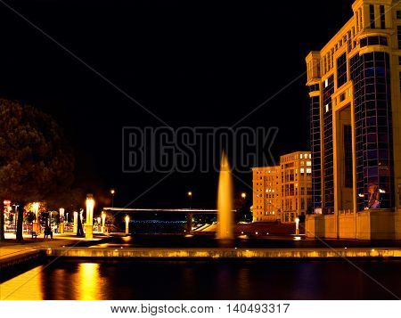 A channel with a fountain at night in Montpellier France