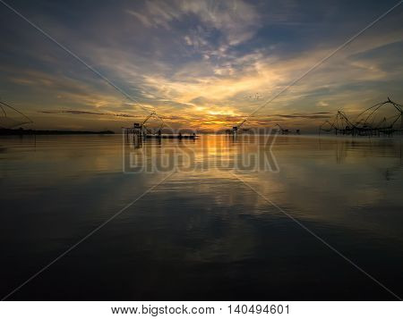 Sunrise and silhouette of fisherman at Thale Noi Waterfowl Park Thailand