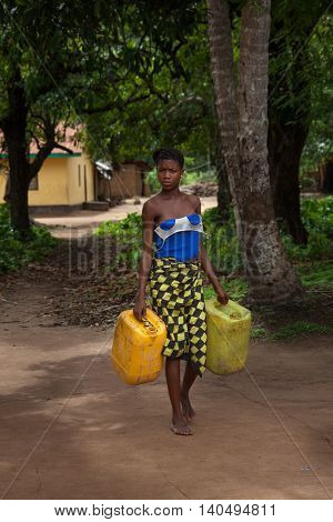 Yongoro Sierra Leone - June 03 2013: West Africa the village of Yongoro in front of Freetown girl carries water cans from artesian well