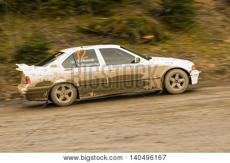 Lviv Ukraine - March 13 2016: Unknown racer on the car brand BMW (No.12) overcome the track at the annual Rally of Winter peaks near the city of Nyzni Worota Ukraine