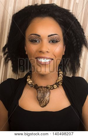 Beautiful smiling black woman is lying on the laminated floor.