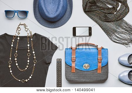 Fashion woman clothes accessories. Creative hipster stylish handbag smartphone black top glamor shoes trendy necklace blue hat and sunglasses.Urban summer outfit. Overhead top view gray background