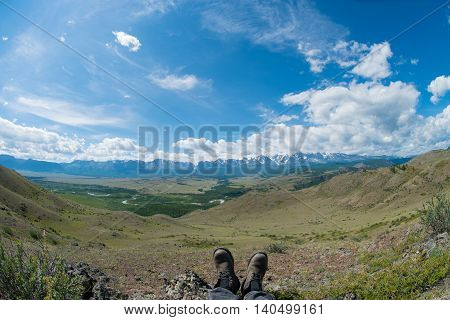 feet in the big shoes against the backdrop of the mountains