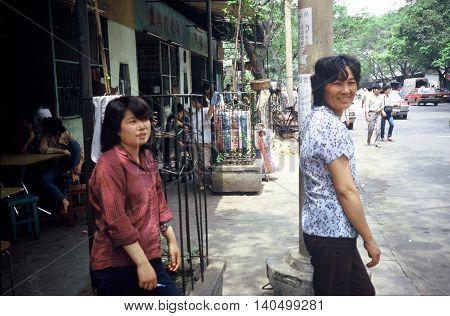 GUANGZHOU / CHINA - CIRCA 1987: Two female pedestrians on the sidewalk in Guangzhou.