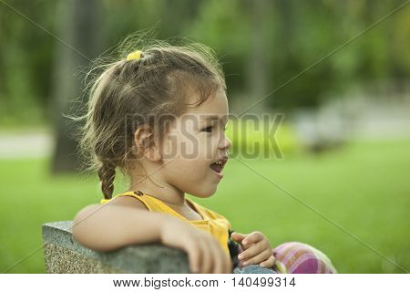 Portrait of the little girl of the vacationer in park