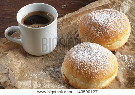 Doughnuts with icing sugar and cup of hot coffee on crumpled paper