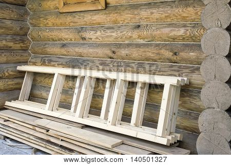 Near the walls of log houses are wooden ladders and planks.