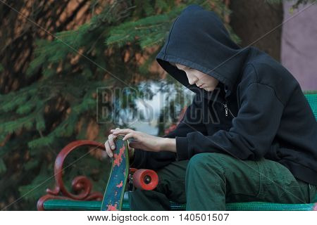 Portrait of relaxing teenager is looking at skateboard in his hands
