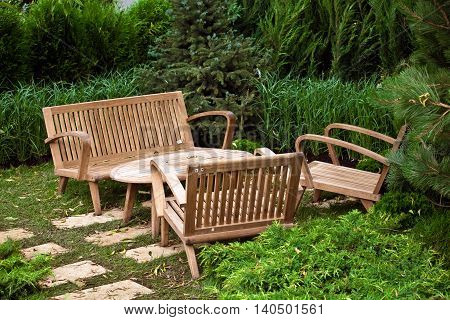 Garden landscape with decorative brown wooden chairs and table