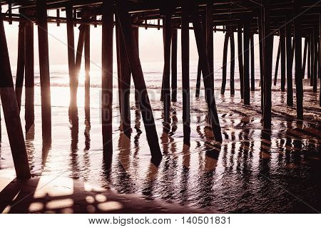 Sun gleaming through wood under pier in ocean