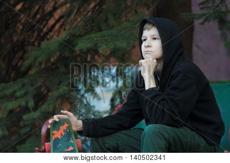 Portrait of daydreaming teenage skateboarder is looking ahead