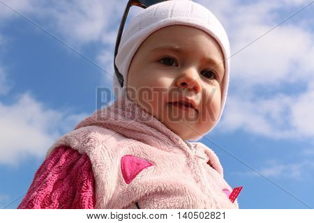 Portrait of a little cute girl in the blue sky and clouds on background