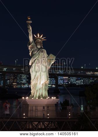 Tokyo - February 3 2015: The illuminated spotlights female figure of the Statue of Liberty with torch in a dark Tokyo Bay in the evening February 3 2015 Tokyo Japan