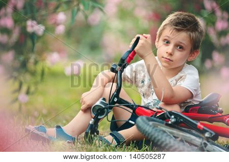 7-years boy sitting in the park with his bicycle.