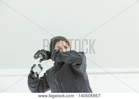 Teen Boy Throwing Snowball Outdoors On Winter Day
