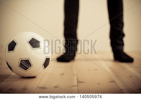 Person Standing Behind Soccer Ball On Wood Floor