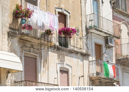 Typical balconies in southern Italian town with drying laundry and flag