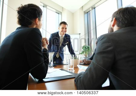 Young man presenting is ideas to colleagues during meeting in conference room. Leader showing business plan to colleagues during a meeting.