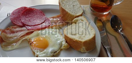 sunny side up eggs bacon and salami with tea for breakfast