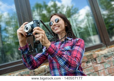Pretty female photographer is taking shots of city. Girl is standing and smiling