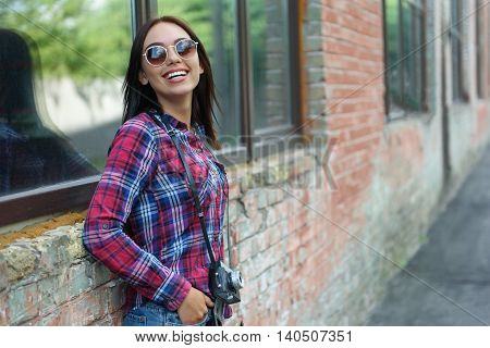 Joyful girl having rest outdoors. She is standing and holding camera. Lady is looking forward and laughing with happiness