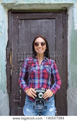 Cheerful female photographer is taking photos. She is standing near door of old building and holding camera. Woman is smiling with happiness