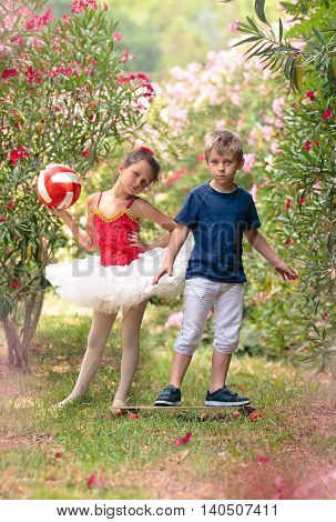 Girl dressed for ballet and boy with skateboard posing in the park.