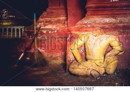 Headless Buddha At The Entrance Of A Cave.