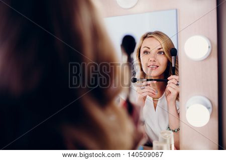 Positive smiling blond girl with make up