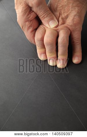 Older man rubs his painful knuckles, copy space included.