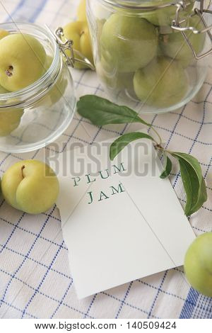 Fresh green plums in glass jars and the words plum jam on paper with copy space