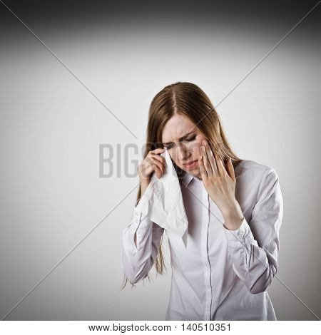 Sad and Unhappy woman in white. Tears welled up in her eyes. Crying concept.
