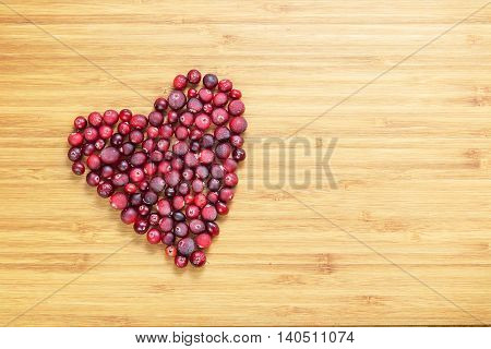 Cranberries in heart shape on wooden board with copy space, horizontal overhead view
