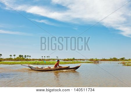 SIEM REAP, CAMBODIA-NOVEMBER 17, 2011: An unidentified man on a boat floating on Tonle Sap lake in Siem Reap. Tonle Sap is the largest lake in SE Asia peaking at 16kkm2