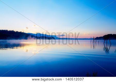beautiful landscape with mountains and lake at dawn in golden, blue and purple tones. Slovakia Liptovska Mara, in region Liptov